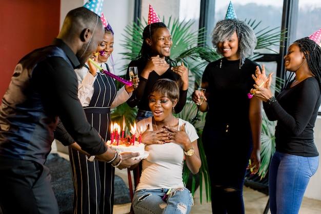 Amici che presentano una torta di compleanno alla ragazza africana