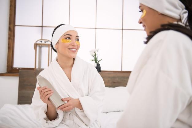 Raccomandazione degli amici giovane donna felice e felice che mostra la lozione per il corpo alla sua amica mentre gliela consiglia