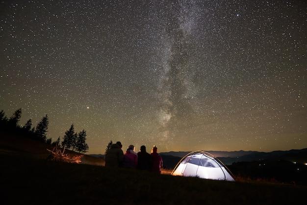 Amici che riposano accanto al campo, falò sotto il cielo stellato notturno