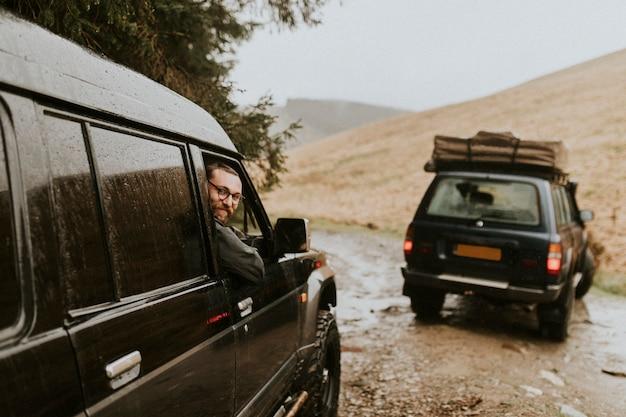 Amici sulla strada che guidano su un terreno accidentato