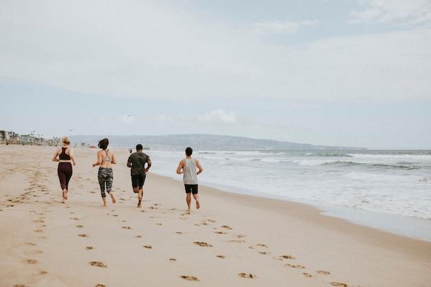 Amici che corrono insieme in spiaggia
