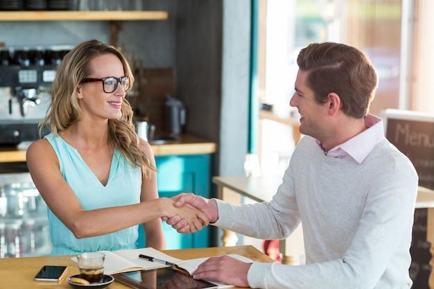 Amici si stringono la mano nel caffè