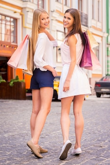 Amici che fanno acquisti. vista posteriore di due belle giovani donne che tengono le borse della spesa e si guardano alle spalle con un sorriso mentre stanno in piedi all'aperto