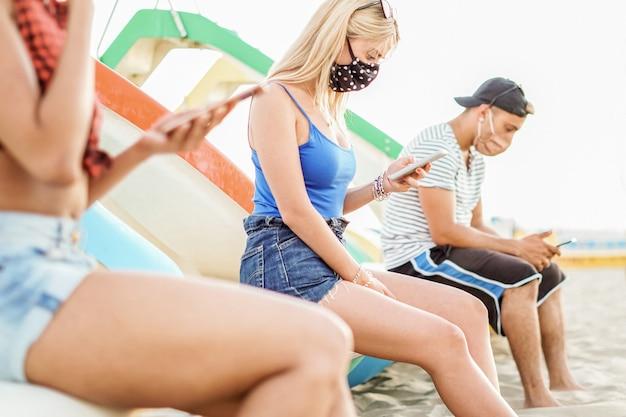 Amici seduti in spiaggia e che usano i loro smartphone a distanza sociale e con la mascherina addosso