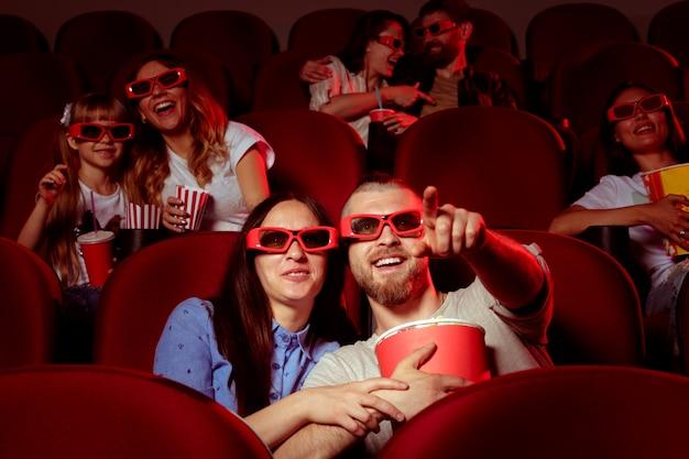 Gli amici seduti al cinema guardano film mangiando popcorn e acqua potabile.