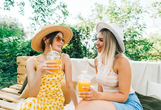 Amici seduti su un divano nel cortile di casa e bevono limonata all'arancia in una giornata di sole estivo.