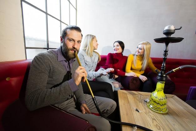 Gli amici fumano il narghilè e si divertono, ridono. l'uomo sorride e guarda la telecamera.