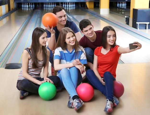 Amici che prendono selfie nel bowling club