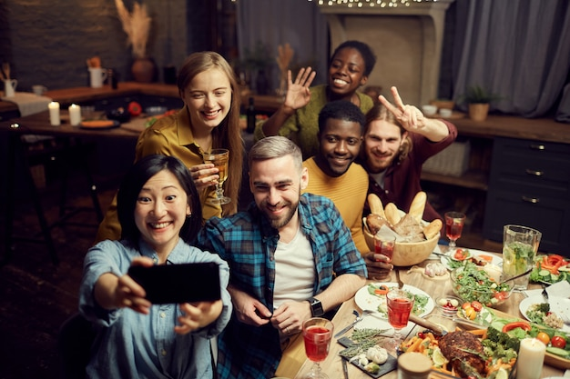 Amici che prendono la foto del selfie a cena