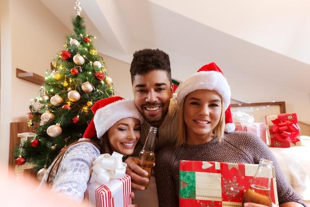 Amici che prendono selfie con regali e birra in mano. s. concetto di vacanze di natale.