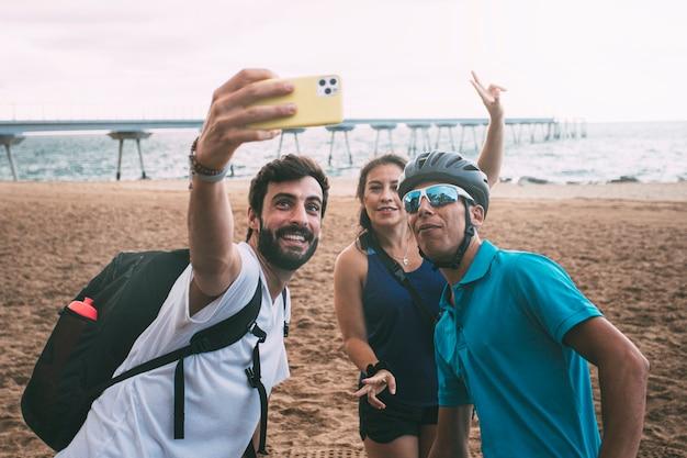 Amici che si fanno selfie con lo smartphone sulla spiaggia vestiti con abiti da ciclismo