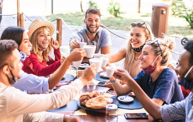 Gli amici che tostano il cappuccino al bar indossano la maschera verso il basso - i giovani si divertono insieme al ristorante - nuovo concetto di stile di vita normale con ragazzi e ragazze felici al bar