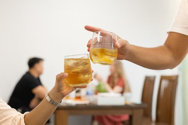 Amici che tostano vetro della celebrazione del whiskey in ristorante.