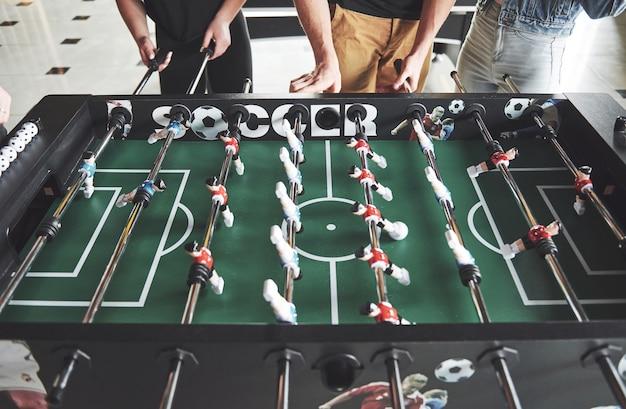 Gli amici insieme giocano a giochi da tavolo, calcio balilla, si divertono nel tempo libero.