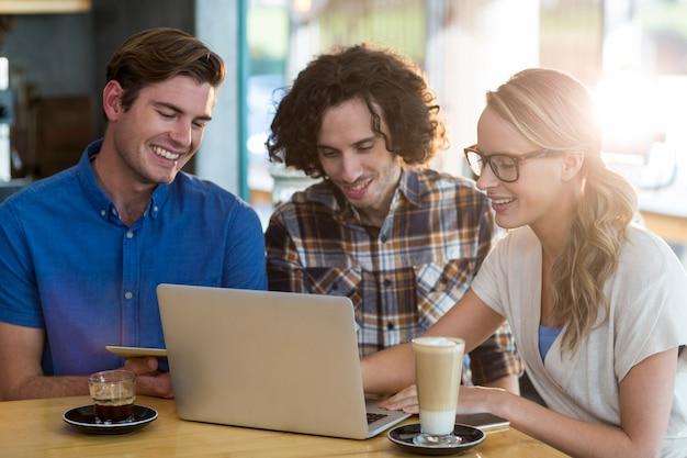 Amici che utilizzano compressa digitale e computer portatile nel caffè