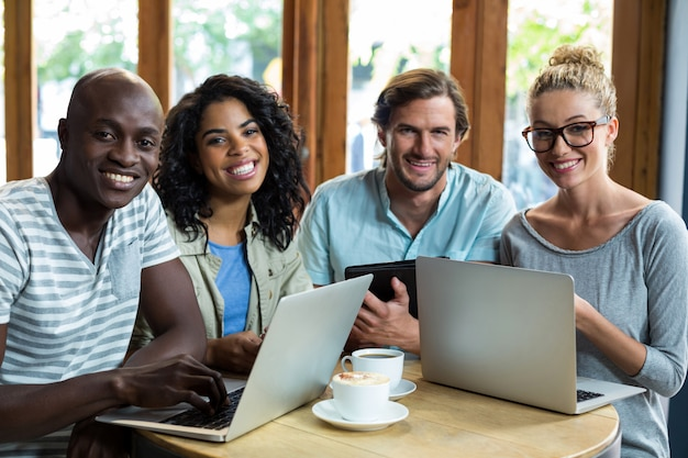 Amici che utilizzano computer portatile e compressa digitale mentre mangiando caffè nel caffè
