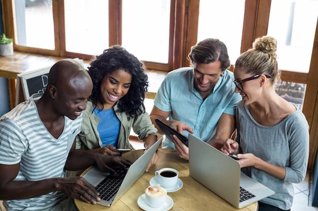Amici che utilizzano laptop, telefono cellulare e tablet digitale mentre si mangia il caffè