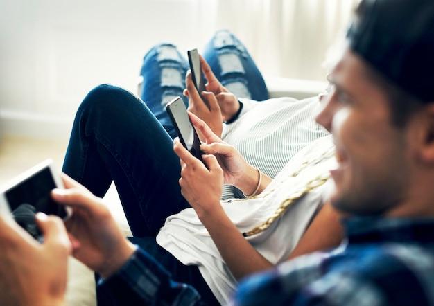 Amici che utilizzano smartphone insieme a casa