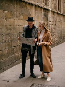 Gli amici camminano con una mappa e una macchina fotografica lungo la strada godendosi una passeggiata insieme.