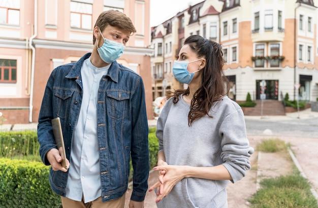 Amici che camminano e chiacchierano all'aperto mentre indossano maschere mediche