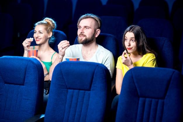 Amici che guardano film seduti insieme a popcorn al cinema