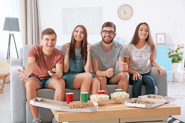 Amici che guardano la tv a casa