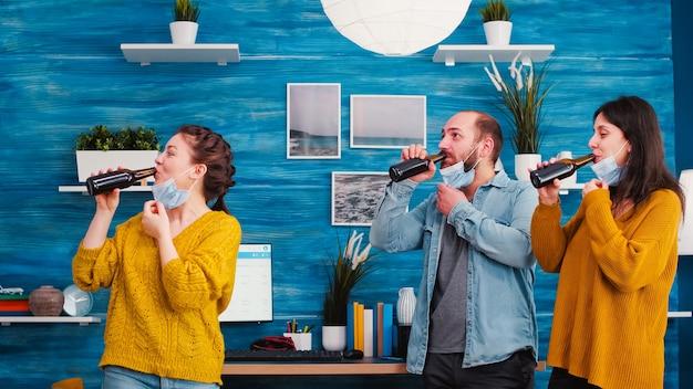 Amici che indossano maschere mediche protettive per il viso per la protezione dalla malattia virale che bevono birra, bottiglie tintinnanti che si divertono durante la nuova festa normale in soggiorno