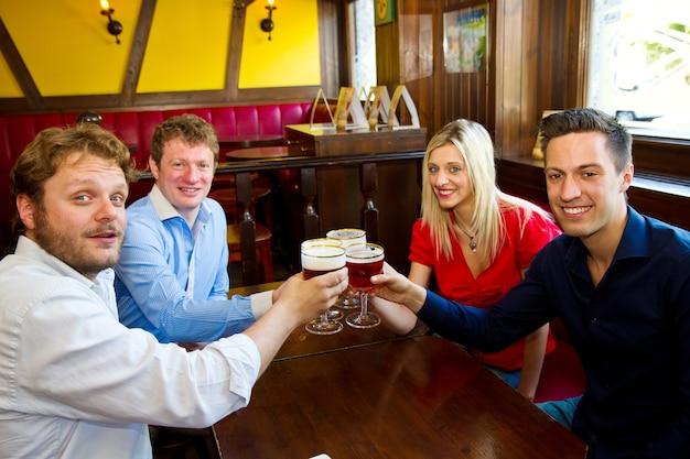 Amici con la birra in un pub