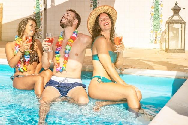 Amici con bevande che si divertono alla festa estiva vicino alla piscina
