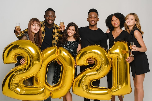 Amici con bicchieri di champagne che tengono 2012 palloncini d'oro su uno sfondo grigio