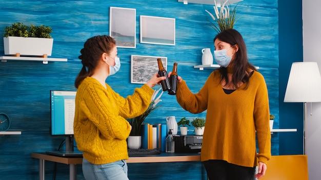 Amici con maschere facciali tintinnanti bottiglie di birra che bevono alla nuova festa normale mantenendo le distanze sociali contro la pandemia di coronavirus prevengono la diffusione del virus
