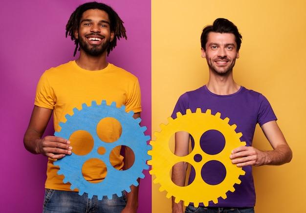 Amici con ingranaggi in mano su sfondo giallo e viola. concetto di integrazione, unione e partenariato