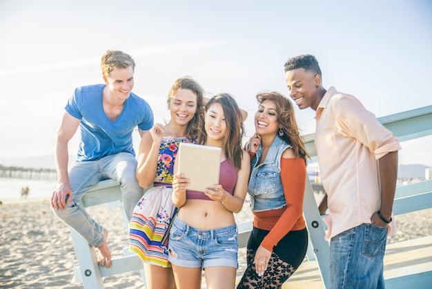 Amici con tablet sulla spiaggia