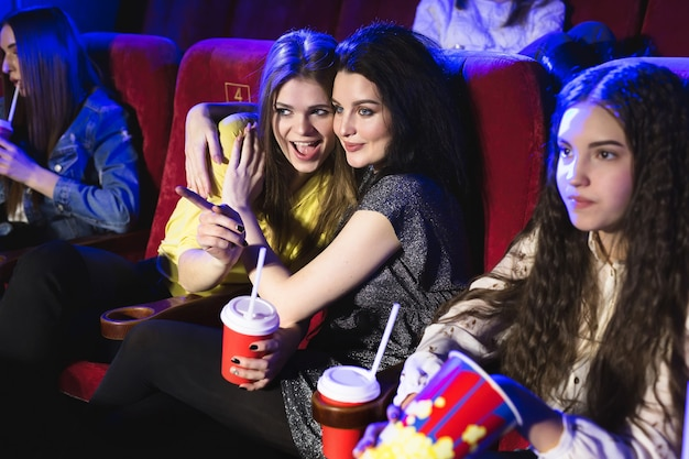 Amici giovani donne al cinema guardano un film, mangiano popcorn e si divertono.