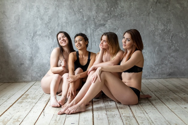 Amicizia, bellezza, corpo positivo e concetto di persone - gruppo di donne felici diverse in biancheria intima su sfondo grigio. foto di alta qualità
