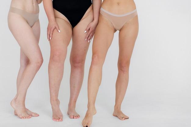 Amicizia bellezza corpo positivo e concetto di persone gruppo di donne felici diverse in biancheria intima su sfondo grigio foto di alta qualità