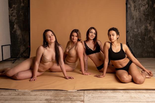 Amicizia, bellezza, corpo positivo e concetto di persone - gruppo di donne felici diverse in biancheria intima su sfondo grigio