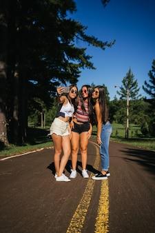Amicizia tra ragazze, divertirsi nel parco e farsi un selfie.