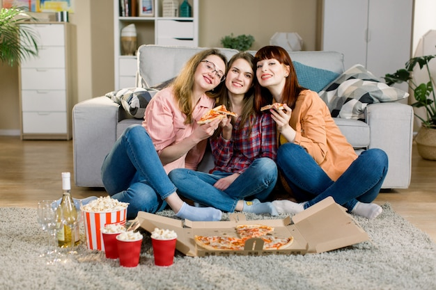 Amicizia, vacanze, fast food e concetto di celebrazione - amici di giovani donne felici con bevande e popcorn che mangiano pizza a casa, seduti sul pavimento in una sala accogliente