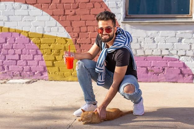 Amicizia tra uomo e gatto sullo sfondo della parete colorata all'aperto.