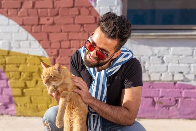 Amicizia tra uomo e gatto sullo sfondo di una parete colorata all'aperto.