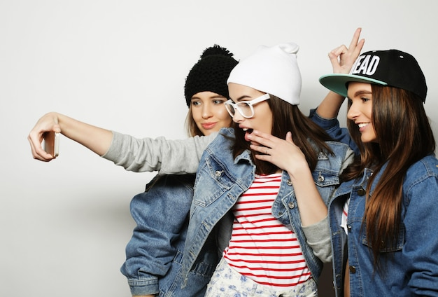 Amicizia, persone e concetto di tecnologia - tre adolescenti felici con lo smartphone che si fanno selfie
