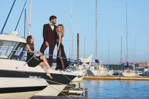 Amicizia e vacanza. festa sullo yacht. gruppo di giovani sul ponte a vela sul mare.