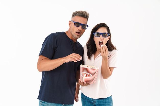 Coppia attraente spaventata che indossa abiti casual in piedi isolati su un muro bianco, guardando un film con popcorn e occhiali 3d