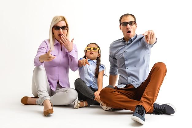 Famiglia attraente spaventata che indossa abiti casual isolati su sfondo bianco, guardando un film con occhiali 3d