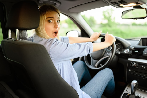 Studentessa spaventata in macchina, lezione di scuola guida. uomo che insegna alla signora a guidare il veicolo.