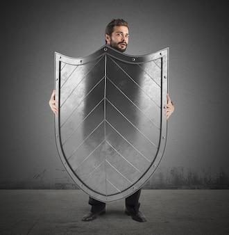 Uomo spaventato che si nasconde dietro un grande scudo