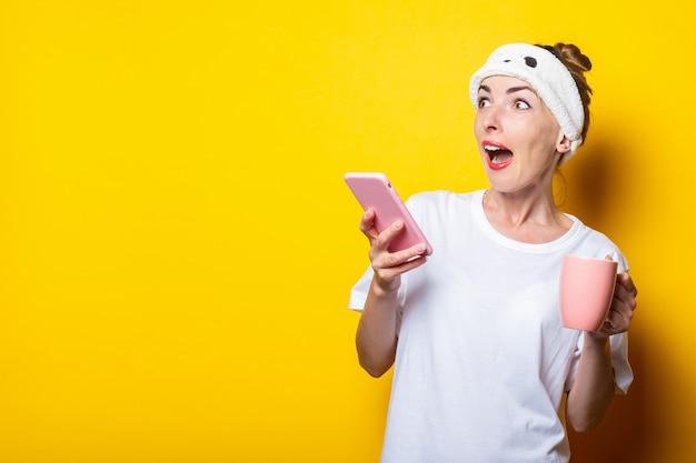 Giovane donna scioccata spaventata in una benda guarda al lato con un telefono e una tazza di caffè su uno sfondo giallo