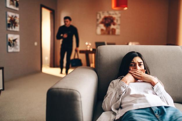 Donna spaventata che si nasconde sul divano, ladro in abiti neri con la borsa in mano è penetrato nell'appartamento.