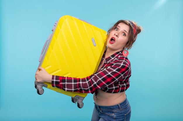 Giovane bella donna spaventata in abiti vintage che tiene una valigia gialla tra le mani in posa su una superficie blu
